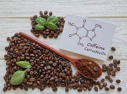 Structural chemical formula of caffeine molecule with roasted coffee beans and wooden spoon filled with coffee powder. Caffeine is a central nervous system stimulant, psychoactive drug molecule.