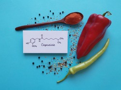 Structural chemical formula of capsaicin molecule with chili peppers, chili powder, and peppercorns. Capsaicin is the compound found in chili peppers that gives them their hot and spicy kick.