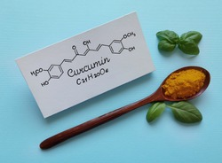 Structural chemical formula of curcumin molecule with wooden spoon filled with turmeric powder (curcuma). Turmeric is an old Indian spice with a powerful medical compound called Curcumin.