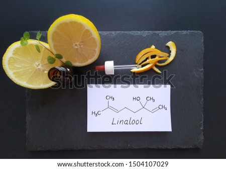 Structural chemical formula of linalool with fresh citrus fruits and a cosmetic glass bottle. Linalool is an aromatic terpene, the major component of essential oils, used in floral fragrances. #1504107029