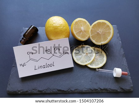 Structural chemical formula of linalool with fresh citrus fruits and a cosmetic glass bottle. Linalool is an aromatic terpene, the major component of essential oils, used in floral fragrances. #1504107206