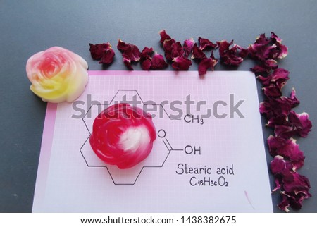 Structural chemical formula of stearic acid molecule with homemade soaps and dried rose petals. Stearic acid is a saturated long-chain fatty acid, used in candle and soap making.