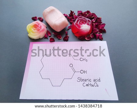Structural chemical formula of stearic acid molecule with homemade soaps and rose petals. Stearic acid is a saturated long-chain fatty acid, used in candle and soap making.