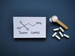 Structural chemical formula of taurine (2-aminoethanesulfonic acid) molecule with taurine pills and white protein powder. Taurine is an amino sulfonic acid, it is often added to energy drinks.