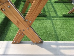 Structural column designed made of wood. Green area with wood plastic composite floor.