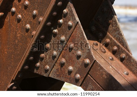 Structural details of a rusty steel cantilever bridge.
