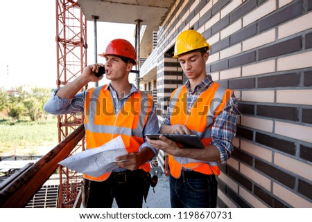 Structural engineer and architect dressed in orange work vests and  helmets discuss the construction process, use a phone and tablet on the balcony of building under construction #1198670731