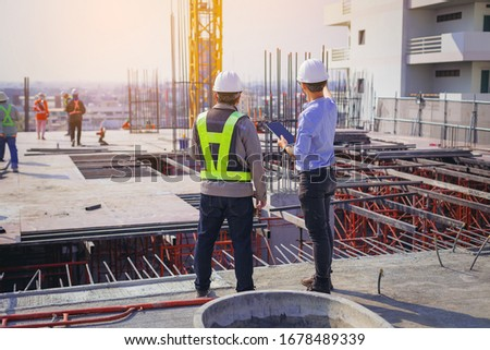 Structural engineer and foreman worker with touch pad discuss, plan working for the outdoors building construction site. ストックフォト ©