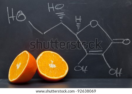 Structural formula of vitamin C on blackboard with orange