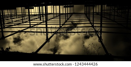 Structural framework with dark cloudy sky background.