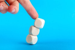 Structure collapsing, knocked over. Wooden cube tower pushed by human finger coming from above. Market collapse, crisis, lack of stability, breakdown and loss of balance abstract concept Cubes falling