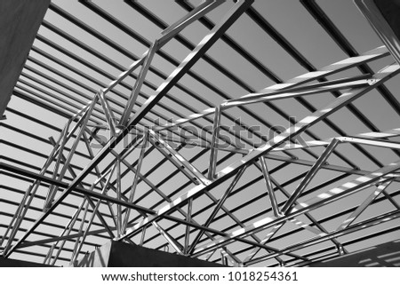 Structure of steel roof frame for building construction. Black and white photo. #1018254361