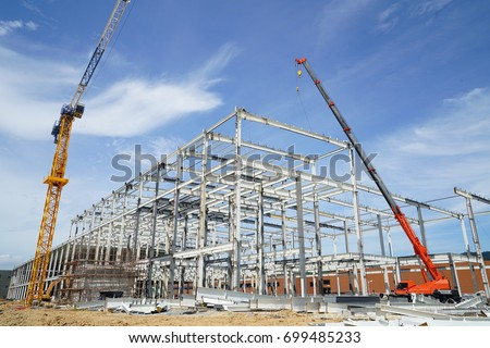 Structure of steel roof frame installation by mobile crane under the building in construction with blue sky  #699485233