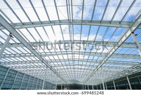 Structure of steel roof frame under the building in construction with blue sky  #699485248