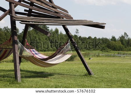 structure with colorful hammocks on grass near wood and pond