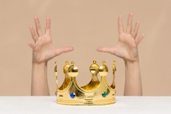 Struggle for the first place. Lust for power concept. A female hands is trying to get a golden crown on the table.