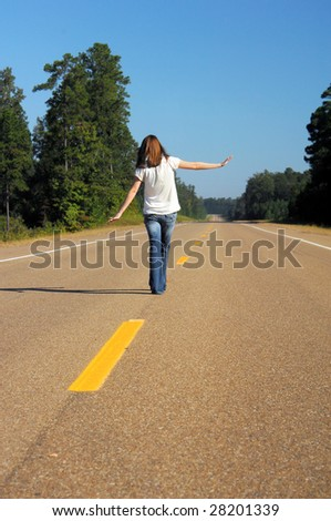 Struggling to balance, teen walks the yellow center line of highway.  Metaphor for \