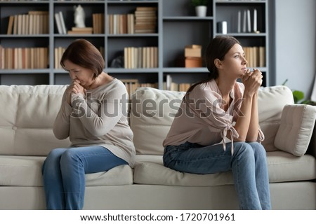 Stubborn adult daughter and mature mother ignoring each other after family quarrel, sitting on couch separately back to back, young woman and upset older mum not talking after fight Stock photo ©