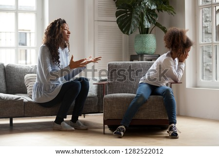 Stubborn african kid ignoring mom scolding lecturing, fussy preschool girl avoiding talk not listening to mum, rebellious daughter and strict mother, black parent and child fight conflict concept