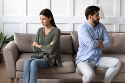 Stubborn angry man and woman spouses sit separate on sofa at home ignore each other avoid talking after fight. Unhappy mad young Caucasian couple think of divorce breakup after family fight quarrel.