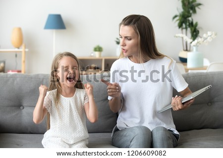 Stubborn little girl scream loud not listening to strict mom, serious young mother scold shouting daughter for bad behavior, working mommy lecture kid yelling asking attention. Family conflict concept