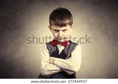 Stubborn,sad,upset  little boy,child  isolated over grey background.Facial expression