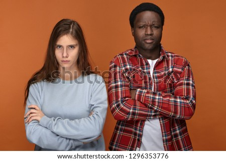 Stubborn young interracial couple having disagreement about plans on weekend looking at camera with grumpy facial expressions, keeping their arms crossed, frowning, not talking to each other