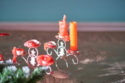 Stubs of red candles on a figured Christmas candlestick with a picture of a fir. The holiday is over
