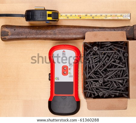 Stud Detector with Screws and Hammer - stock photo