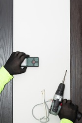 Stud finder (metal and cable detector) and drill in hands of handyman on the wall background.
