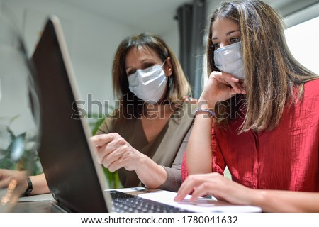 Student and her teacher wearing protective mask and working a lesson on  a laptop at home during lockdown due to covid-19