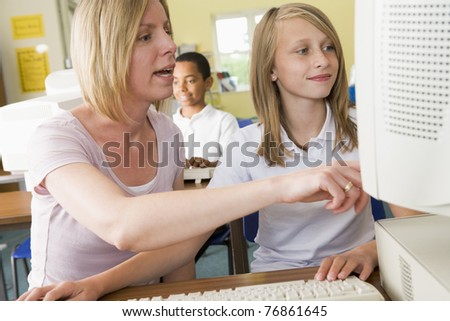 Student and teacher at computer terminal with student in background