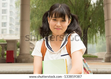 Student asian girl outside in summer green park smiling happy. Female college or university student holding books