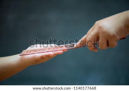 Student being physically punished by teacher with a ruler on on wooden blackboard or chalkboard background.