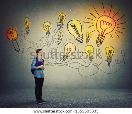 Student boy holding books and backpack imagining bright lightbulbs on the wall. Smart and ingenious teen guy has different thinking, genius creativity concept, alternative idea as the way to success. #1555503833