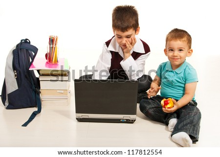 Student boy using laptop  while his little brother eating an apple and sitting together on floor