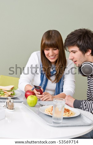 Student cafeteria - teenage couple with mobile phone during lunch break