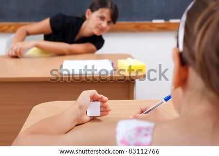 Student cheating while writing test, teacher is looking at her