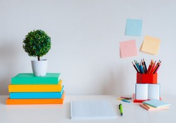 Student creative desktop layout with colorful stationery, colored pencils and bright books on a white wall background. Back to school. free space