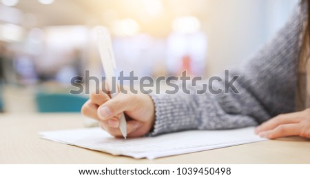 Student doing her homework, writing on note in library