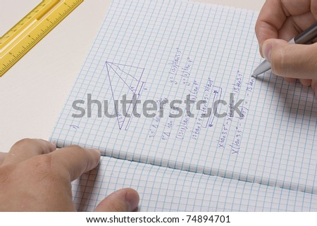 Student doing math homework in a notebook.
