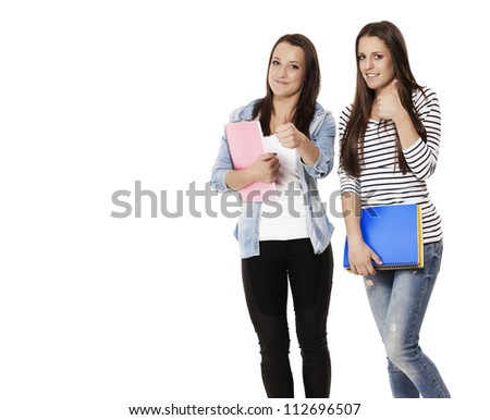 student female teenagers with notepads showing thumbs up on white background