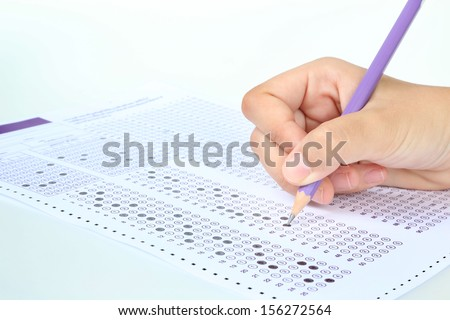 Student filling out answers to purple answer sheet with purple pencil