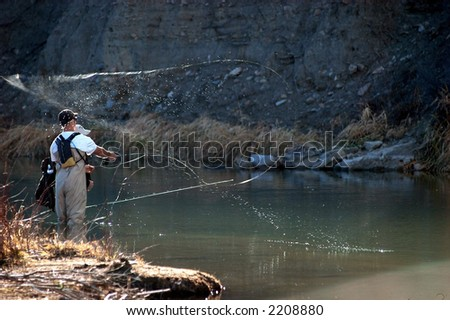 student fly casting from river bank with line action