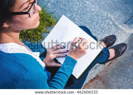 Student girl holding notebook and pencil. Young beautiful woman writing notes #462606535