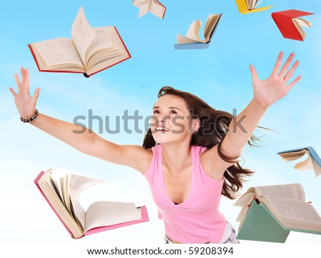 Student girl holding pile of books. Outdoor.