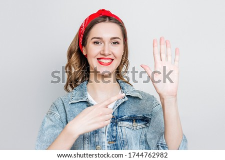 Photo of  Student girl in denim jacket, bandana smiles and points to her left hand isolated on gray background, left-handed woman celebrating left-handed day