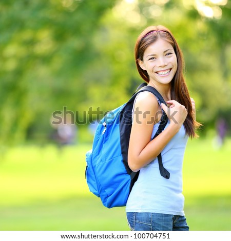 Student girl outside in summer park smiling happy. Asian female college or university student. Mixed race Asian / Caucasian young woman model wearing school bag.
