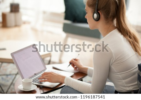 Student girl sitting at home looking at laptop screen listening exercise, studying foreign languages online making notes, side view. Call center operator working indoors. Technology e-learning concept