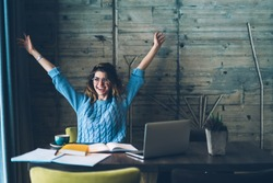 Student girl sitting at table with open notebook and raises hands up while smiling with sincere happiness. 